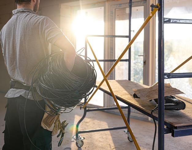 Un electricista examina un dibujo de construcción mientras sostiene un cable eléctrico en su mano en un sitio de trabajo.