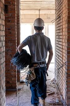 Un electricista examina un dibujo de construcción mientras sostiene un cable eléctrico en su mano en un sitio de trabajo