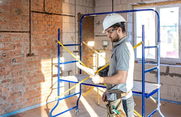 Un electricista examina un dibujo de construcción en un sitio de trabajo