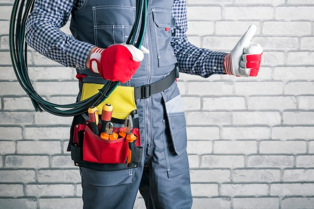 Electricista con herramientas sosteniendo alambres enrollados y mostrando el pulgar hacia arriba contra el fondo de la pared de ladrillo.