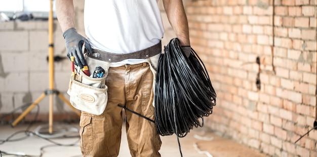 Electricista con herramientas, trabajando en un sitio de construcción. concepto de reparación y manitas.