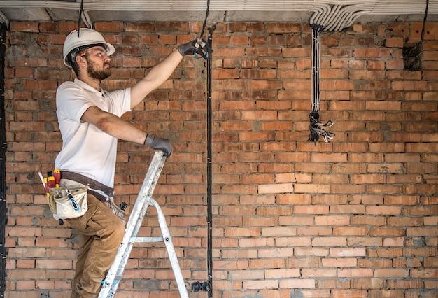 Electricista con herramientas, trabajando en un sitio en construcción
