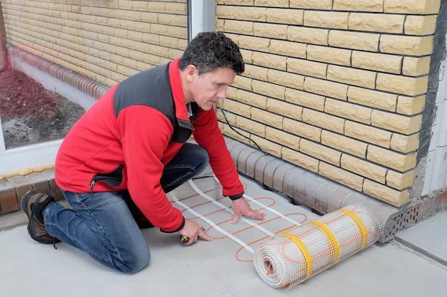 Electricista instalando calefacción cable eléctrico en piso de cemento.