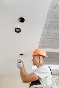 El electricista está instalando focos led en el techo.