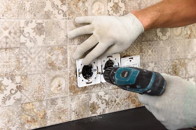 Un electricista está instalando interruptores y enchufes en la pared.