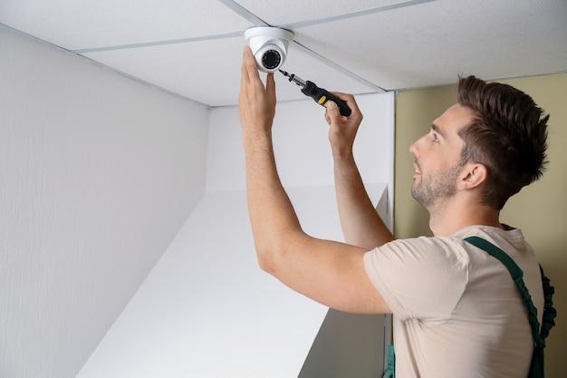 Electricista instalando sistema de alarma en interiores