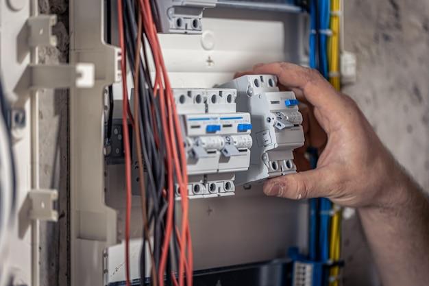 Un electricista masculino trabaja en una centralita con un cable de conexión eléctrica