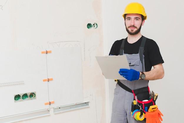 Electricista de pie con la carpeta de papel