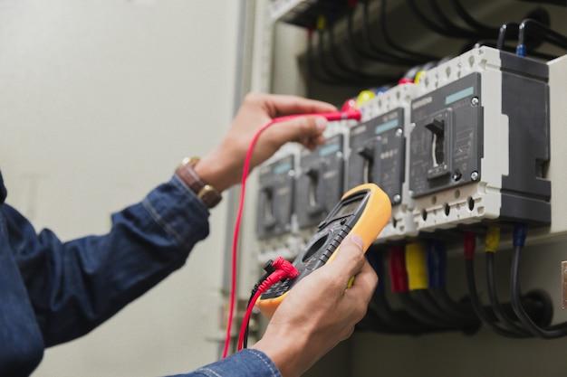 Electricista probador de trabajo de medición de voltaje de línea eléctrica de potencia.