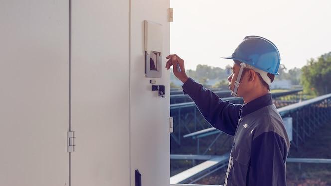 Electricista que trabaja en la comprobación e inspección de equipos con lista de verificación en la industria al aire libre