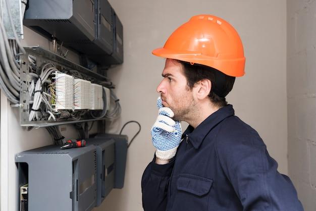 Electricista de sexo masculino que mira la placa de circuito y que piensa
