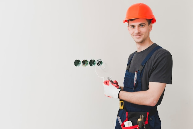 Electricista sonriente en los agujeros del enchufe
