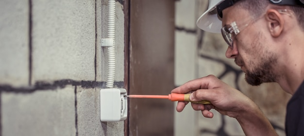 Electricista-técnico masculino, conecta el equipo con una herramienta