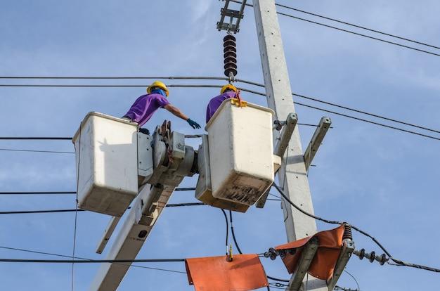Electricista trabaja en postes eléctricos.