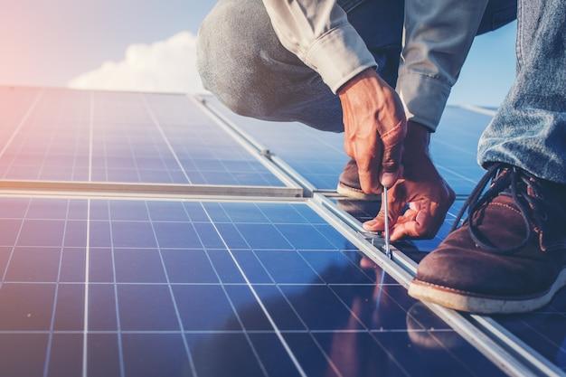 Un electricista trabajando en el apriete de la llave en la estructura de montaje solar