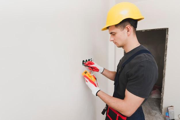 Electricista trabajando con herramienta de medida
