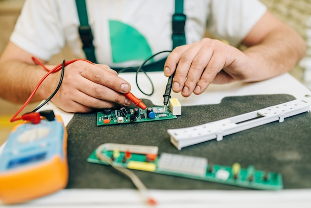 Electricista en uniforme comprueba el chip, manitas