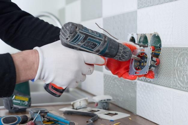 Electricistas instalando a mano toma de corriente en la pared con baldosas de cerámica con herramientas profesionales