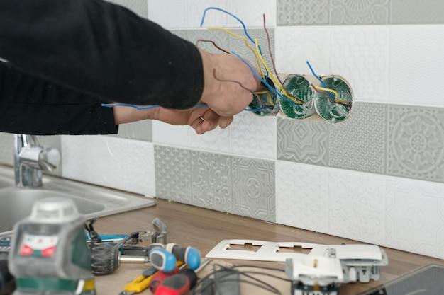 Electricistas instalando toma de corriente en la pared con azulejos de cerámica