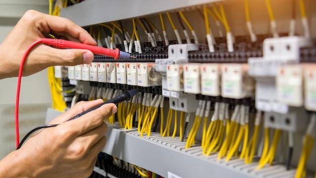 Electricistas manos probando corriente eléctrica en panel de control.