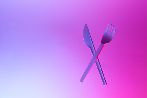 Los electrodomésticos desechables de plástico blanco tenedor y cuchillo levitan en luz de neón, fondo azul rosa, espacio de copia.