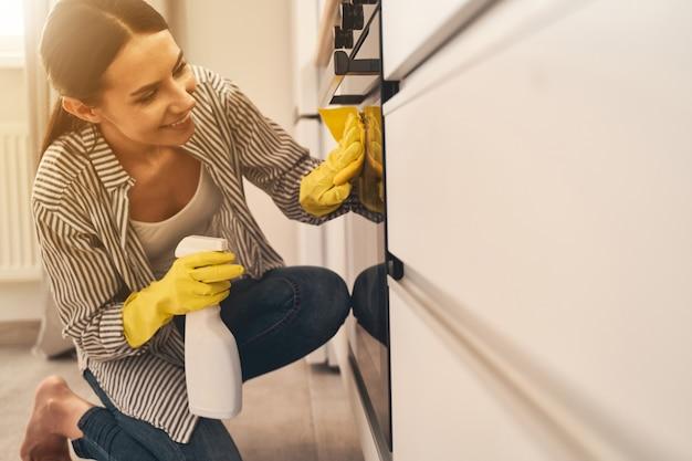 Electrodomésticos. pretty woman manteniendo una sonrisa en su rostro mientras trabaja en casa con placer