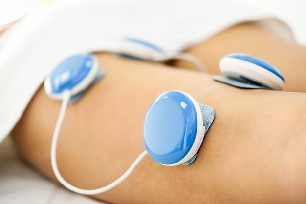 Electroestimulación en fisioterapia a una pierna de mujer joven.