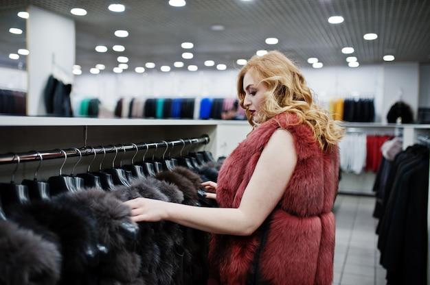 Elegancia chica rubia en abrigo de piel en la tienda de abrigos de piel y chaquetas de cuero.