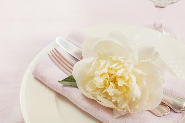 Elegancia mesa puesta con planta en mantel de lino rosa