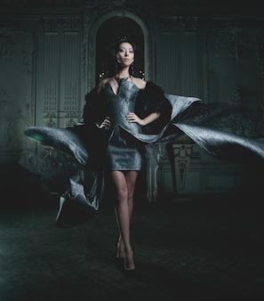 Elegancia mujer con vestido volador en sala de palacio
