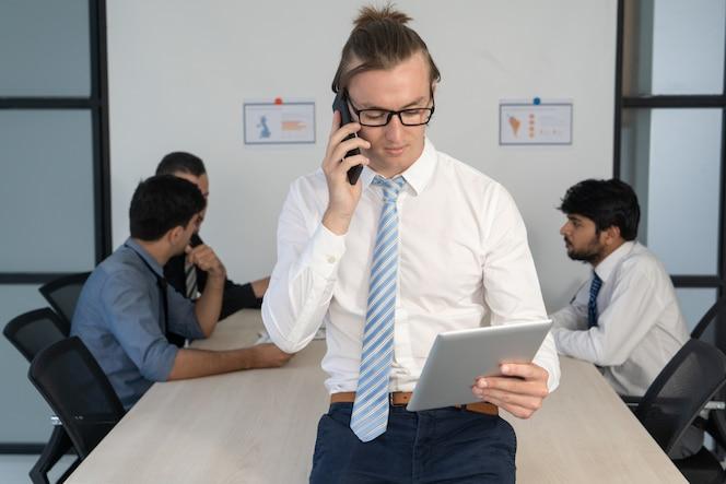 Elegante actualización de datos de jóvenes expertos con teléfono y tableta.