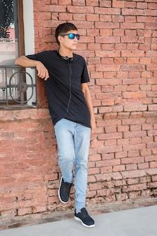 Elegante adolescente apoyado en una pared de ladrillos y escuchando música.