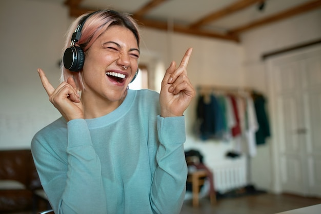 Elegante adolescente con cabello rosado y perforaciones faciales divirtiéndose en el interior, estando sola en casa, escuchando música en auriculares inalámbricos, cerrando los ojos, haciendo movimientos de baile, cantando con