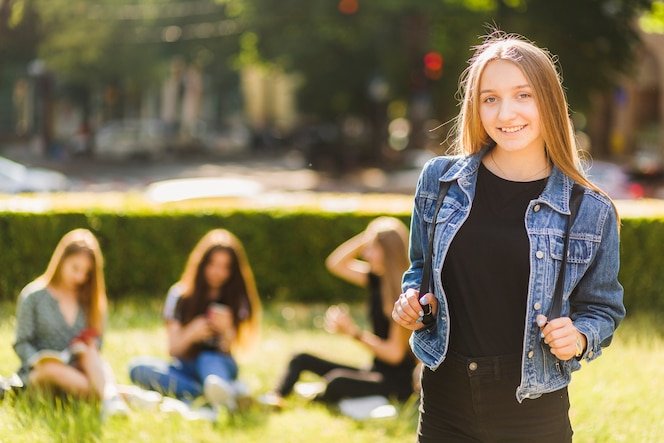 Elegante adolescente parado cerca de amigos