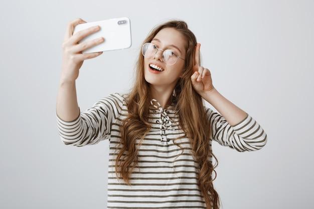 Elegante adolescente tomando selfie en smartphone, sonriendo feliz