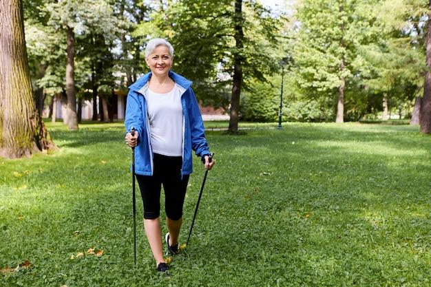 Elegante y alegre anciana vestida con ropa deportiva admirando la hermosa naturaleza salvaje en la pacífica mañana de verano, caminando con palos especiales, con una amplia sonrisa alegre