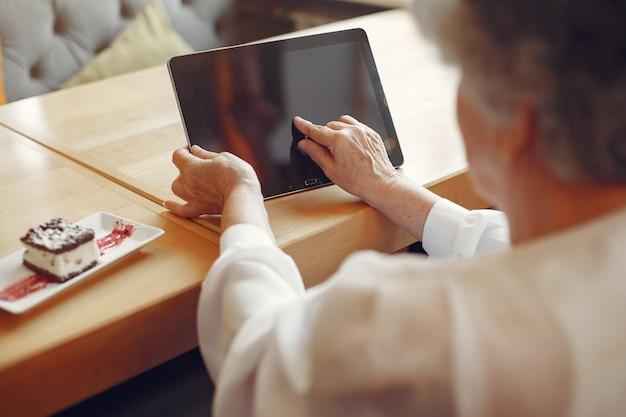 Elegante anciana sentada en un café y usando una computadora portátil
