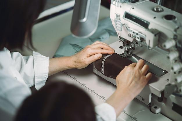 Elegante anciana sentada en estudio y coser tela