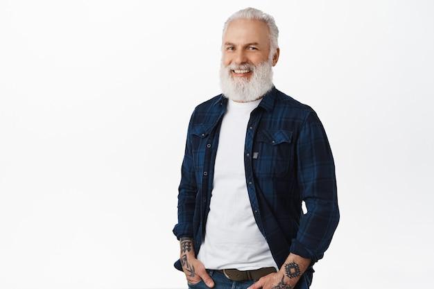 Elegante anciano con barba y tatuajes, de pie relajado con las manos en los bolsillos, mirando a un lado la pancarta del logotipo con una sonrisa complacida, de pie sobre una pared blanca