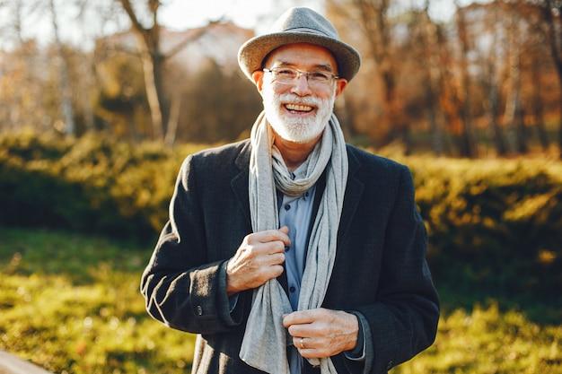 Elegante anciano en un parque soleado de otoño