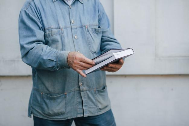 Elegante anciano de pie sobre fondo gris con un libro