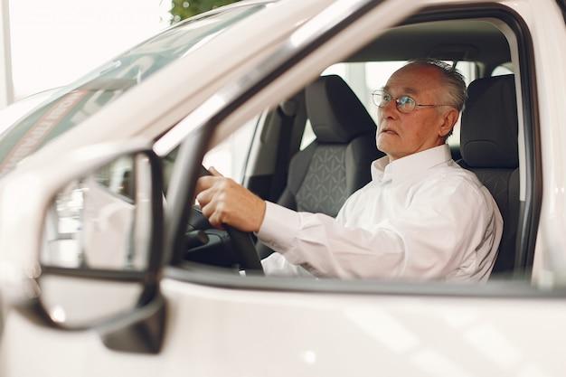 Elegante anciano en un salón del automóvil