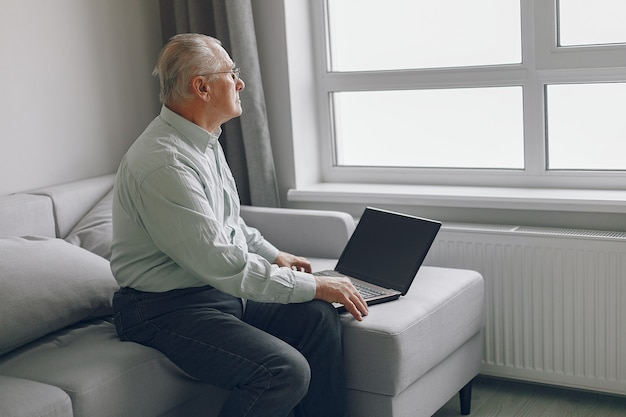 Elegante anciano sentado en casa y usando una computadora portátil