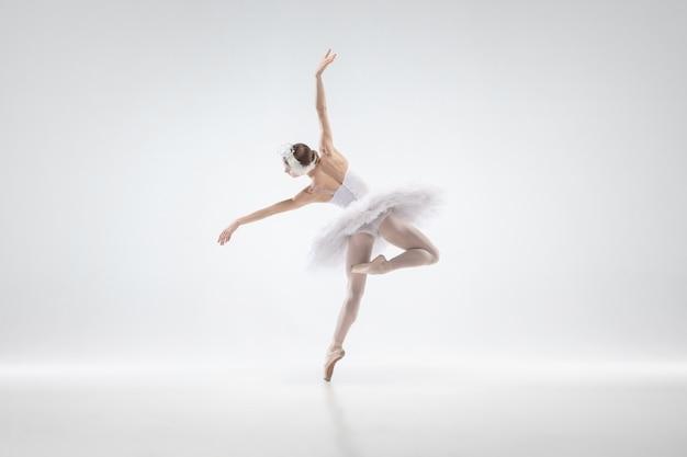 Elegante bailarina clásica bailando aislado sobre fondo blanco de estudio. mujer con ropa tierna como personajes de cisne blanco. el concepto de gracia, artista, movimiento, acción y movimiento. parece ingrávido.