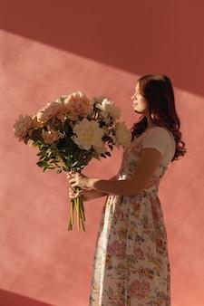 Elegante bella mujer con ramo de flores
