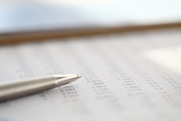 El elegante bolígrafo plateado descansa sobre el informe con números