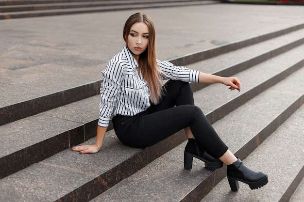 Elegante y bonita mujer joven americana en jeans negros en una elegante blusa a rayas con zapatos de cuero descansando sobre los viejos pasos de la ciudad en un cálido día de primavera