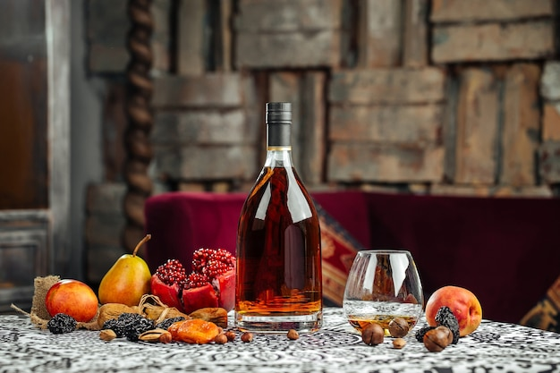 Elegante botella de coñac con frutas sobre la mesa