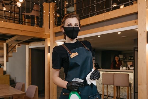 Una elegante camarera que usa un delantal, una mascarilla médica negra y guantes médicos desechables sostiene una botella con desinfectante y un trapo blanco en un restaurante
