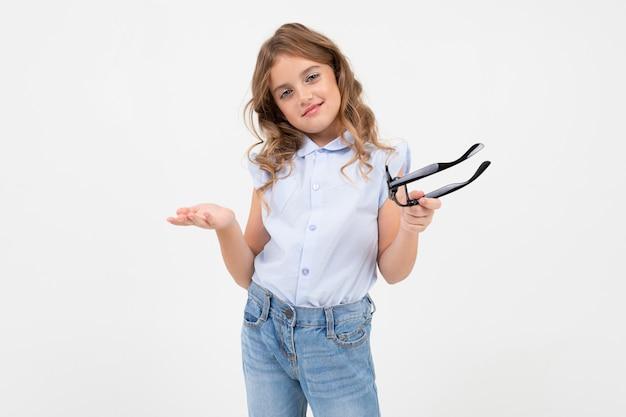 Elegante chica adolescente se quitó los anteojos para la visión y sostiene en su mano un blanco con espacio de copia